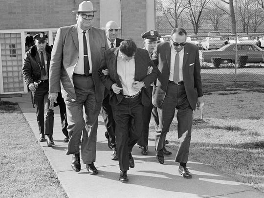 James Earl Ray lowers his head as Tennessee Safety Commissioner Greg O'Rear, white hat, and Tennessee Highway Patrol Maj. Mickey McGuire, dark glasses, lead him to prison in Nashville on March 11, 1969, to serve a 99-year sentence in the death of Dr. Martin Luther King Jr. in Memphis. (AP Photo)