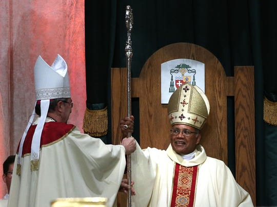 The Most Rev. Martin D. Holley, right, is presented his crosier, a staff that is curved at the top to remind him of a shepherd's crook, during his Solemn Installation to appoint him Fifth Bishop of the Diocese of Memphis, Tennessee held at the Cook Convention Center.