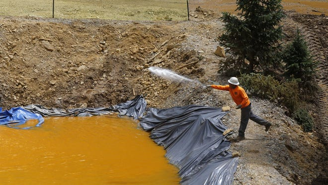 An employee with Environmental Restoration LLC tends to a temporary water treatment holding facility on Aug. 10 at the Gold King Mine north of Silverton, Colo.