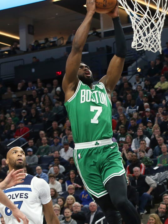 Boston Celtics's Jaylen Brown lays up as Minnesota Timberwolves' Taj Gibson, left, looks on in the first half of an NBA basketball game Thursday, March 8, 2018, in St. Paul, Minn. (AP Photo/Jim Mone)