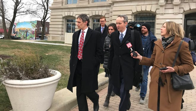 Jeff Miller, far left, and his attorney, James Bell, leave Hendricks County Courthouse Friday, Dec. 15, 2017, trailed by news media.