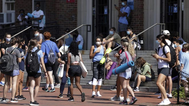 UNC students wait outside of Woolen Gym on the Chapel Hill, N.C. campus as they wait to enter for a fitness class Monday. The university announced minutes before that all classes will be moved online starting Wednesday due to COVID clusters on campus.