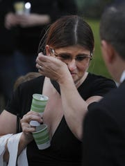 Lisa Gassett, wife of one of the victims of a shooting rampage, wipes away tears during a candlelight vigil Thursday, April 20, 2017 in Fresno, Calif.