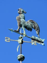 A rooster decorates this weather vane.