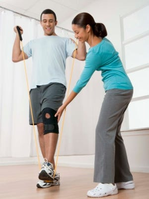 A physical therapist helps a patient in rehabilitation.