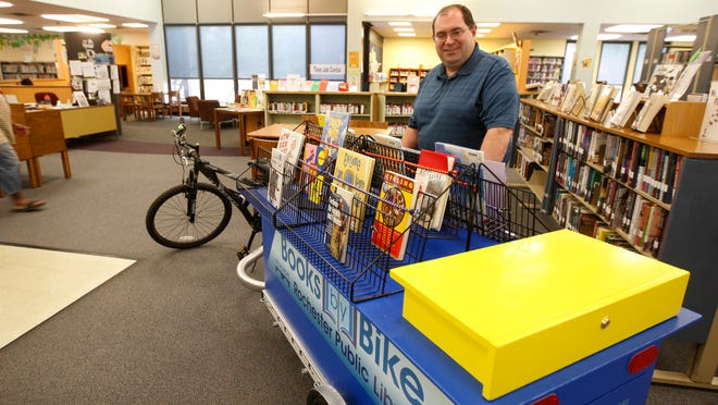 Bruce Tehan, site supervisor at Arnett Branch Library, with the library's new outreach and marketing tool, Books by Bike, on May 11, 2015.