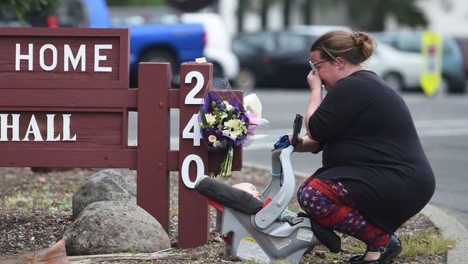 A woman, who declined to give her name, cries after placing flowers at a sign at the Veterans Home of California, on Saturday, the morning after a hostage situation in Yountville.  A daylong siege at The Pathway Home ended Friday evening with the discovery of four bodies, including the gunman, identified as Albert Wong, a former Army rifleman who served a year in Afghanistan in 2011-2012.