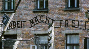 """A view of the gates leading into the Auschwitz concentration camp. The sign reads """"Work Sets You Free"""""""