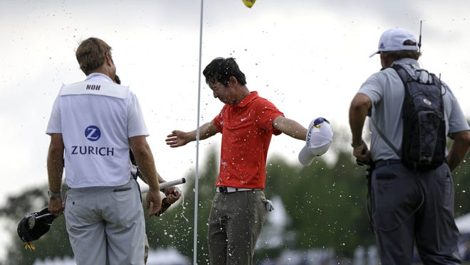 Seung-yul Noh, center, of South Korea, is doused with beer on the 18th green after winning the Zurich Classic golf tournament at TPC Louisiana in Avondale, La., Sunday, April 27, 2014.