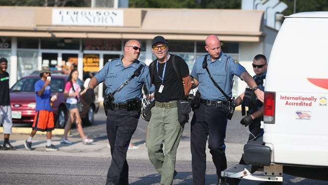 Getty Images staff photographer Scott Olson is placed into a paddy wagon after being arrested by police as he covers the demonstrations following the Aug. 9 shooting death of Michael Brown, on August 18, 2014 in Ferguson, Mo.