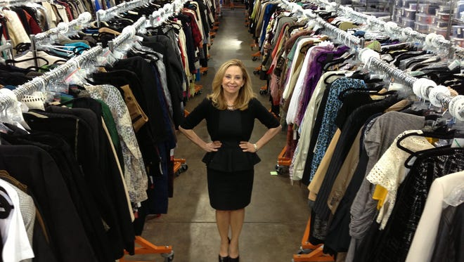 Julie Wainwright, founder and CEO of TheRealReal.com, stands amid racks of pre-owned high-end luxury goods that are sold through her site.