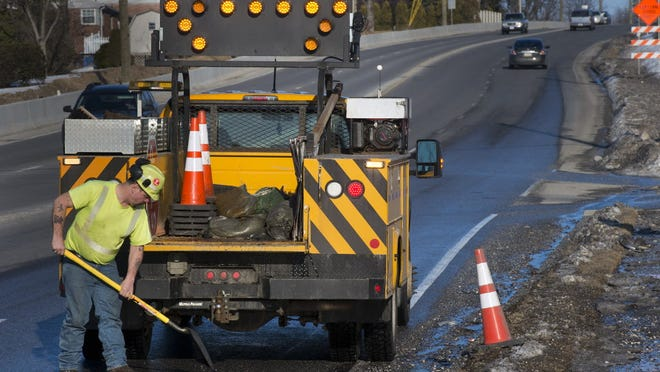 A PennDOT worker fills a pothole in York County in this 2015 photo. Potholes along Interstate 83 have been particularly bad this year, and crews have been out working on them, with more work to come.