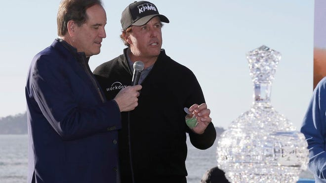 From Feb. 11, 2019, while being interviewed by CBS Sports broadcaster Jim Nantz, left, Phil Mickelson holds up a silver dollar that belonged to his grandfather during an awards ceremony on the 18th green of the Pebble Beach Golf Links after winning the AT&T Pebble Beach Pro-Am golf tournament, in Pebble Beach, Calif. Nantz has worked the Final Four and Masters for the last 34 years and is missing them in 2020 because of the new coronavirus pandemic.