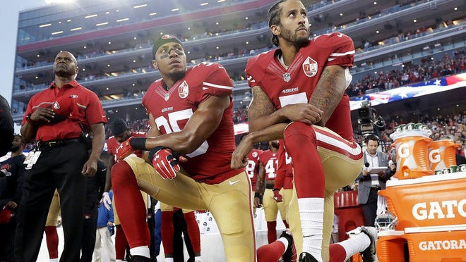 San Francisco 49ers safety Eric Reid (35) and quarterback Colin Kaepernick (7) kneel during the national anthem before a September 2016, football game against the Los Angeles Rams in Santa Clara, Calif.