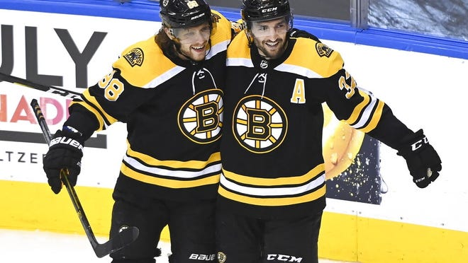Patrice Bergeron celebrates his goal with teammate David Pastrnak (88) during second period against Carolina in Toronto on Wednesday.