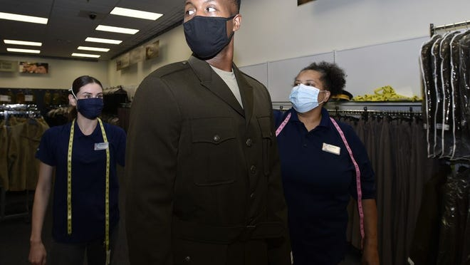 Staff Sgt. Shomone Hemphill, a drill sergeant assigned to Company D, 31st Engineer Battalion, is fitted for his new Army Green Service Uniform Tuesday at the Army and Air Force Exchange Service clothing sales by AAFES inventory control associates Anissa Bibbs-Ward (right) and Kristina Storey. More than 280 Fort Leonard Wood drill sergeants are scheduled to get fittings for the new uniform this month.