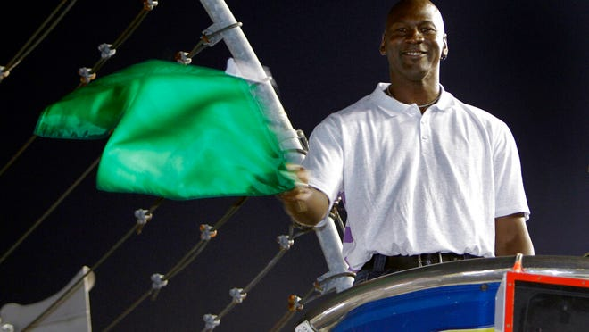 FILE - In this May 22, 2010, file photo, Charlotte Bobcats owner Michael Jordan practices waving the green flag before a NASCAR All-Star auto race at Charlotte Motor Speedway in Concord, N.C. Denny Hamlin is starting his own race car team in partnership Jordan and Bubba Wallace as the driver.