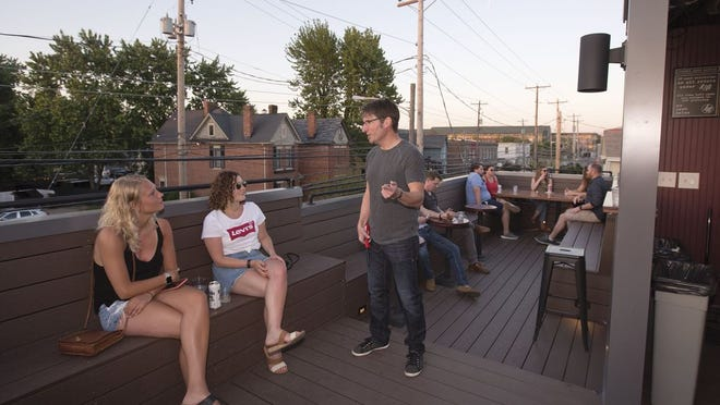 Little Rock Bar owner Quinn Fallon chats with patrons on the Italian Village bar's rooftop patio in 2018.