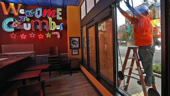Workers install a new window in Melt Bar & Grilled in the Short North on June 5. The windows were damaged during recent protests in Columbus.