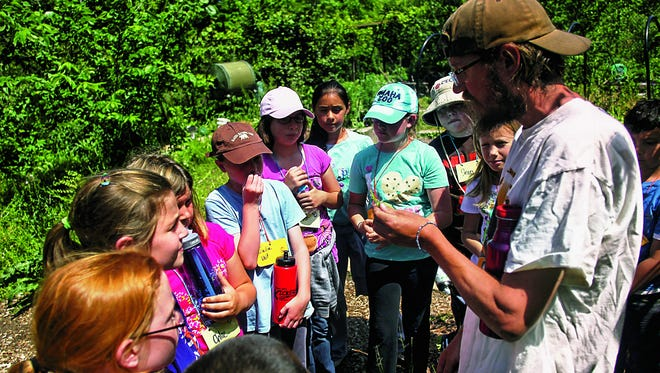 Jason Jensen, co-director of School of the Wild, talks about perennial plants with Lucas Elementary students at Macbride nature area on May 15, 2012.