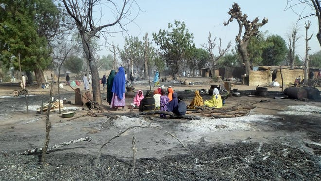 Women and children sit among burnt houses after Boko Haram attacks at Dalori village on the outskirts of Maiduguri in northeastern Nigeria on Jan. 31, 2016.