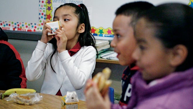 Juliet Cabellero, 7, drinks a carton of juice while having breakfast in her first-grade classroom at Ramirez Thomas Elementary School on Wednesday.