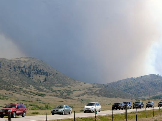 A line of vehicles head east as authorities closed Larimer County Road 74E between The Forks and Glacier View Meadows after winds and dry weather ingnited the High Park Fire Friday June 22, 2012. Lightning sparked the fire, which started June 9, 2012, and was 100 percent contained by June 30, 2012. It killed one woman, burned 87,284 acres and destroyed 259 homes, making it the third-most destructive and third-largest wildfire in Colorado history.