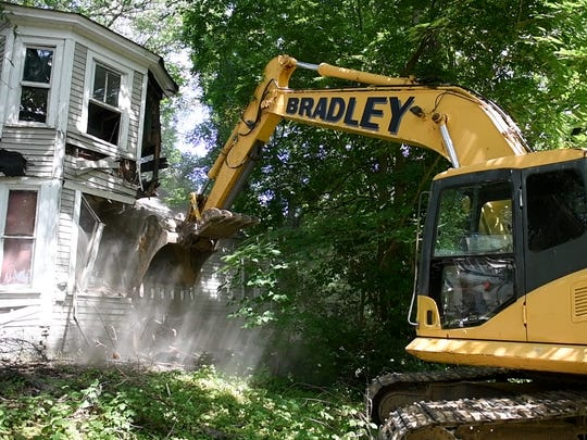 An excavator is used to demolish the vacant house located at 133 W. Deaderick Street in downtown Jackson, Wednesday, July 12. The building was the first to be demolished in Jackson under Tennessee's Blight Elimination Program.