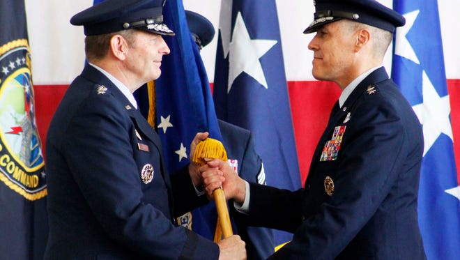 Commander of Air Force Global Strike Command, Gen. Robin Rand (left)  passes the flag to the new 8th Air Force commander Maj. Gen. Thomas Bussiere  during the change of command ceremony at Barksdale Air Force Base Tuesday Oct. 4 in Bossier City