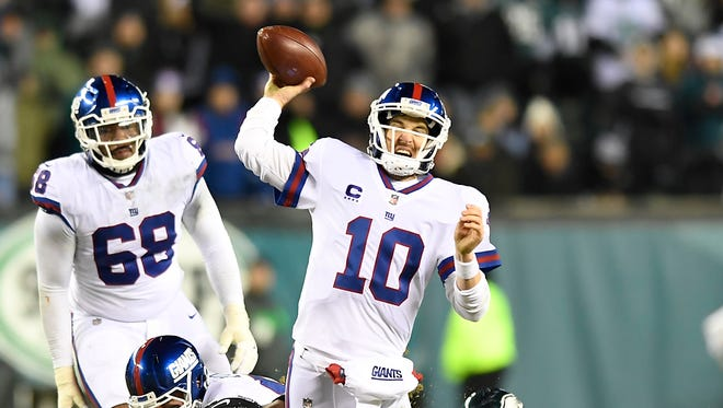 New York Giants quarterback Eli Manning (10) gets rid of the ball just as he's hit by the Eagles defense at Lincoln Financial Field in Philadelphia, PA on Thursday, December 22, 2016.