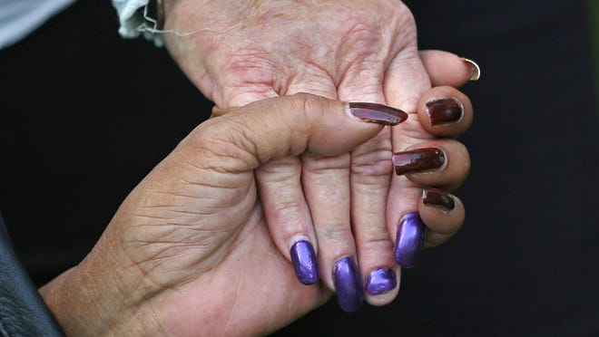 """People hold hands as they gather in prayer at a """"Stop the Violence"""" picnic in Denver Park, Sunday, July 12, 2015."""