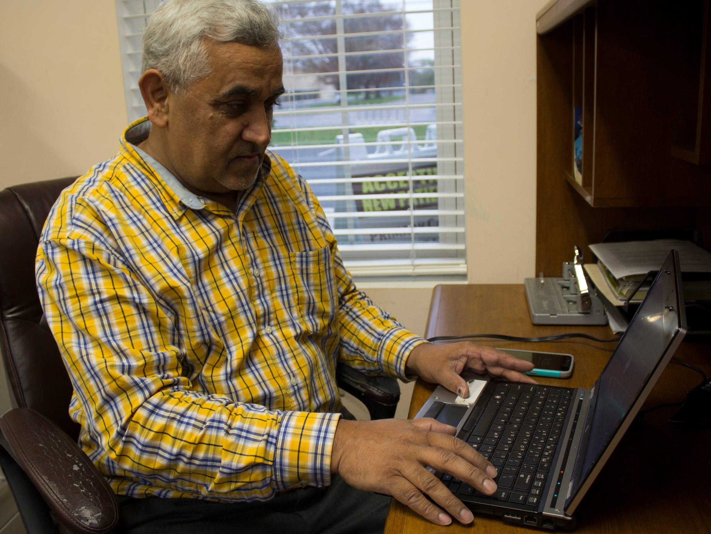 Akram Khalid works at his desk the morning of Nov.