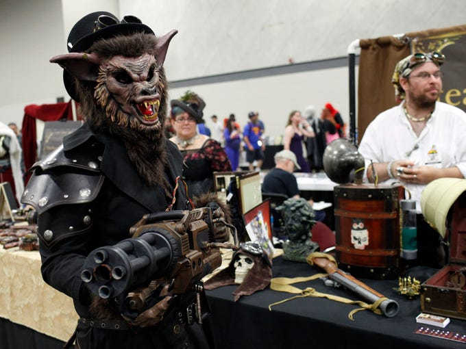 Jon Keith, left, dressed as a Steampunk wolf, and Michael Crawford, right, display historical science fiction gadgetry during the Derby City Comic Con held at the Kentucky  International Convention Center. The two day event features over 225 exhibitors and comic creators.   June 28, 2014