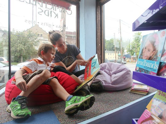 Lincoln and Ann Swintosky read together in the window seating area during the grand opening of Carmichael's Kids on Bardstown Road in Louisville, KY. Aug. 10, 2014