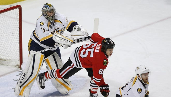 Predators goaltender Pekka Rinne, left, pushes Blackhawks center Andrew Shaw (65) away from the net in the first period Tuesday.