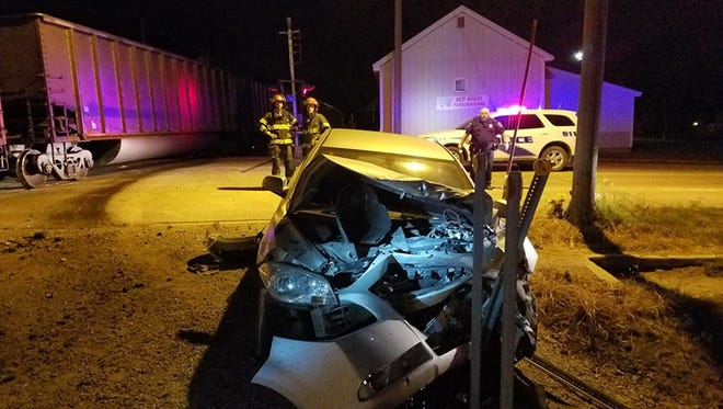 Emergency officials look at the vehicle owned by Devin Stephan, Marengo, which was struck by a westbound train in Belle Plaine on Aug. 9. He was not injured. He was charged with OWI.