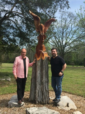 """Dan Miller, left, and Chad Jeffers flank """"Aristotle,"""" an eagle carved from a cedar tree on the property of Miller's home and conference facility in Franklin."""