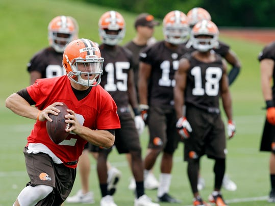 ADVANCE FOR WEEKEND EDITIONS, JULY 19-20 - FILE - In this June 11, 2014, file photo, Cleveland Browns quarterback Johnny Manziel runs the ball during NFL football minicamp at the team's facility in Berea, Ohio. With LeBron James' return, Johnny Football might not be the top star in Cleveland, but Manziel will still get plenty of attention for what he does on and off the field this summer.  (AP Photo/Mark Duncan, File)
