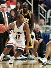 FILE -- Connecticut's Khalid El-Amin, left, prepares to drive on Iowa's Dean Oliver, right, at the NCAA West Regionals in Phoenix on Thursday, March 18, 1999. Connecticut won 78-68 and advances to the regional finals Saturday against Gonzaga. Iowa's Joey Range is behind El-Amin.