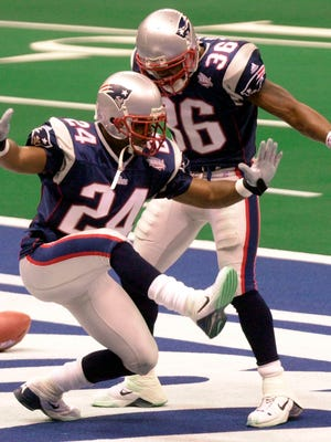 In this Feb. 3, 2002, file photo, New England Patriots cornerback Ty Law (24) celebrates with teammate Lawyer Milloy after Law's interception of a pass by St. Louis Rams' Kurt Warner for a touchdown during the second quarter of Super Bowl XXXVI in New Orleans. Law, who played on the first three title teams in New England, was inducted to Canton in 2019.