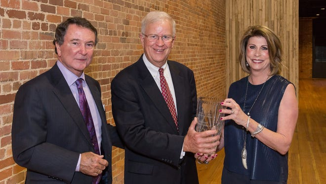 Dave Borden, center, presents the 2016 Tocqueville Society Award to Barrie Harmon III, left, and his wife, Laura Harmon, during the society's dinner, hosted at The Warehouse at Alley Station.