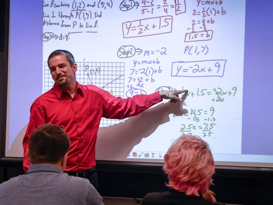 Academy for Innovative Studies teacher David Steckel points to one of the steps needed to solve a class problem in geometry class.