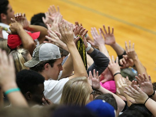 Anderson University fans hold up their hands while a Trojan player shoots a free throw against Erskine, where 1,043 showed up for the rivalry matchup.