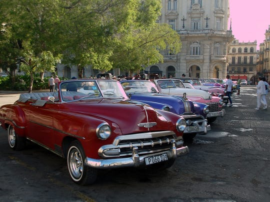 This row of vintage cars is a taxi stand in Havana awaiting passengers. Historic buildings can be seen in the background.