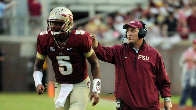 Sep 21, 2013; Tallahassee, FL, USA; Florida State Seminoles quarterback Jameis Winston (5) returns to the field after talking with head coach Jimbo Fisher during the first half of the game against the Bethune-Cookman Wildcats at Doak Campbell Stadium. Mandatory Credit: Melina Vastola-USA TODAY Sports