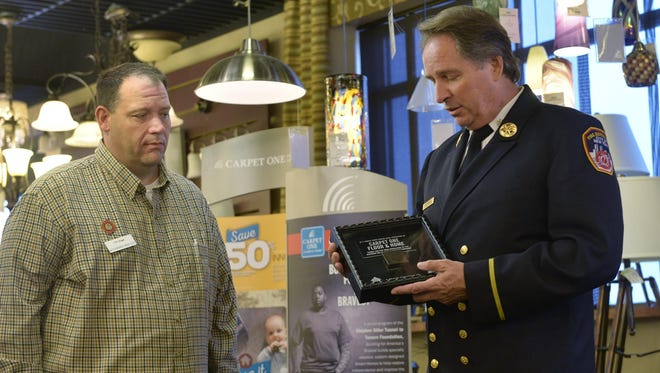 New York City Fire Department Battalion Chief John Martorana, right, talks about a shadow box with a piece of recovered steel from the World Trade Center with Tim Engel, sales manager at MCI Carpet One, during a presentation Tuesday afternoon in Waite Park.