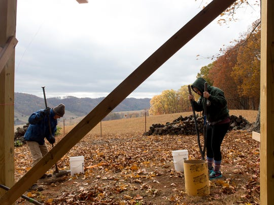 Bill Nickle, left, and Abby Lancaster dig post holes on a lease site at Narrow Ridge on Nov. 19, 2016. Lancaster, who is majoring in sustainability at UT, is volunteering her time to help the homeowner build a yurt.