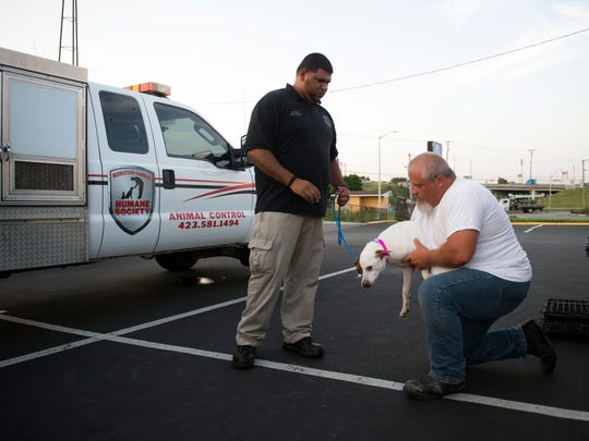 Officer Jose RoJas, left, of the Morristown Hamblen Humane Society hands over Daisy to Scott Gunter before she is loaded onto the GoNorth van.
