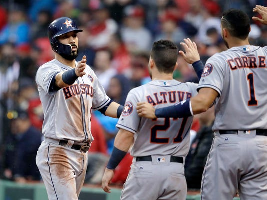 Houston Astros's Marwin Gonzalez, left, is congratulated by Jose Altuve, middle, and Carlos Correa, right, after scoring on a Carlos Beltran single during the ninth inning in Game 4 of baseball's American League Division Series against the Boston Red Sox, Monday, Oct. 9, 2017, in Boston. (AP Photo/Charles Krupa)