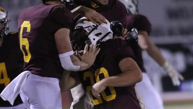 Dylan Dreiling (6) and Hays High assistant coach Layton Hickel celebrate with Dalton Dale after Dale's pick six late in Hays High's 29-6 over Dodge City on Friday night at Lewis Field.
